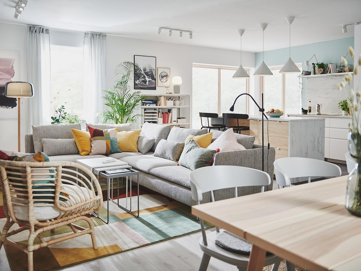 Stue med mørk turkis sofa og taburet, en hvid opbevaringsløsning og et mørk blågrønt skab.