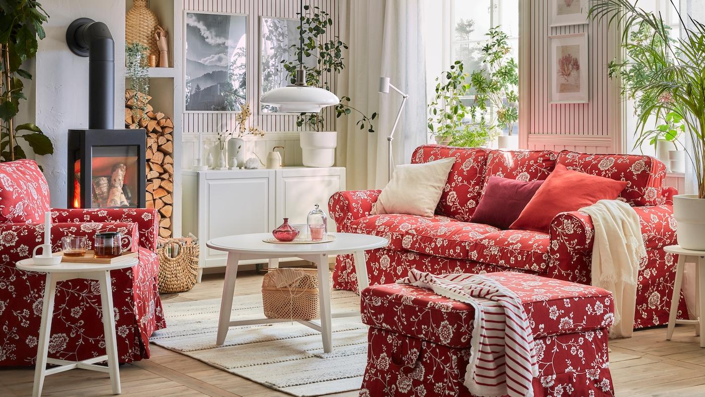 Stue med rød-/hvitblomstret EKTORP sofa, lenestol og fotskammel, runde bord og en skjenk.