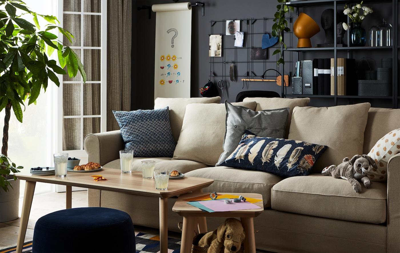 Stue med sofa og bord med origami og kosemat.
