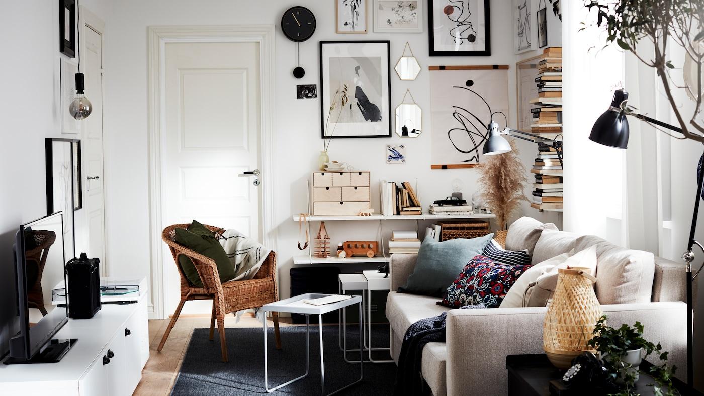 Stue med sovesofa, stol af rotting/bambus, tv-bord, mørkegråt tæppe, sort vægur og sorte lamper.