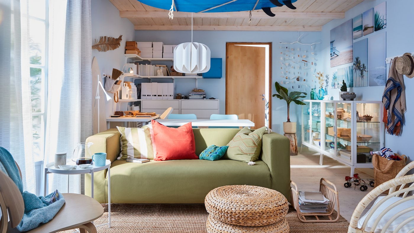 Stue med surfing-tema med en gulgrøn sofa, et blåt surfboard i loftet, hvide hylder og blå vægge.