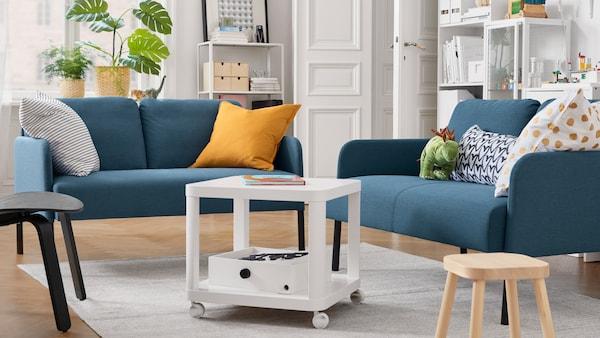 Stue med to 2-pers. sofaer, et hvidt sofabord med hjul, en taburet til børn, puder og potteplanter.