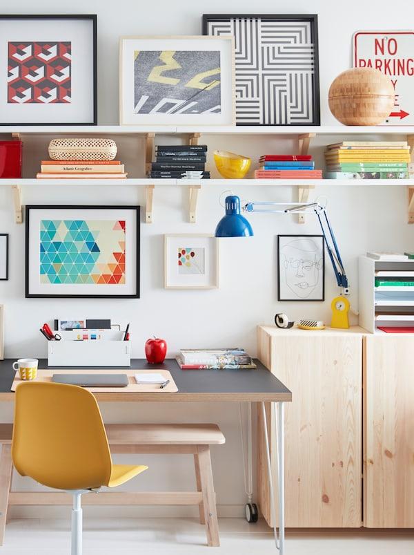 Stůl na kolečkách u stěny, kolem je světlý nábytek ze série IVAR a police s obrázky.