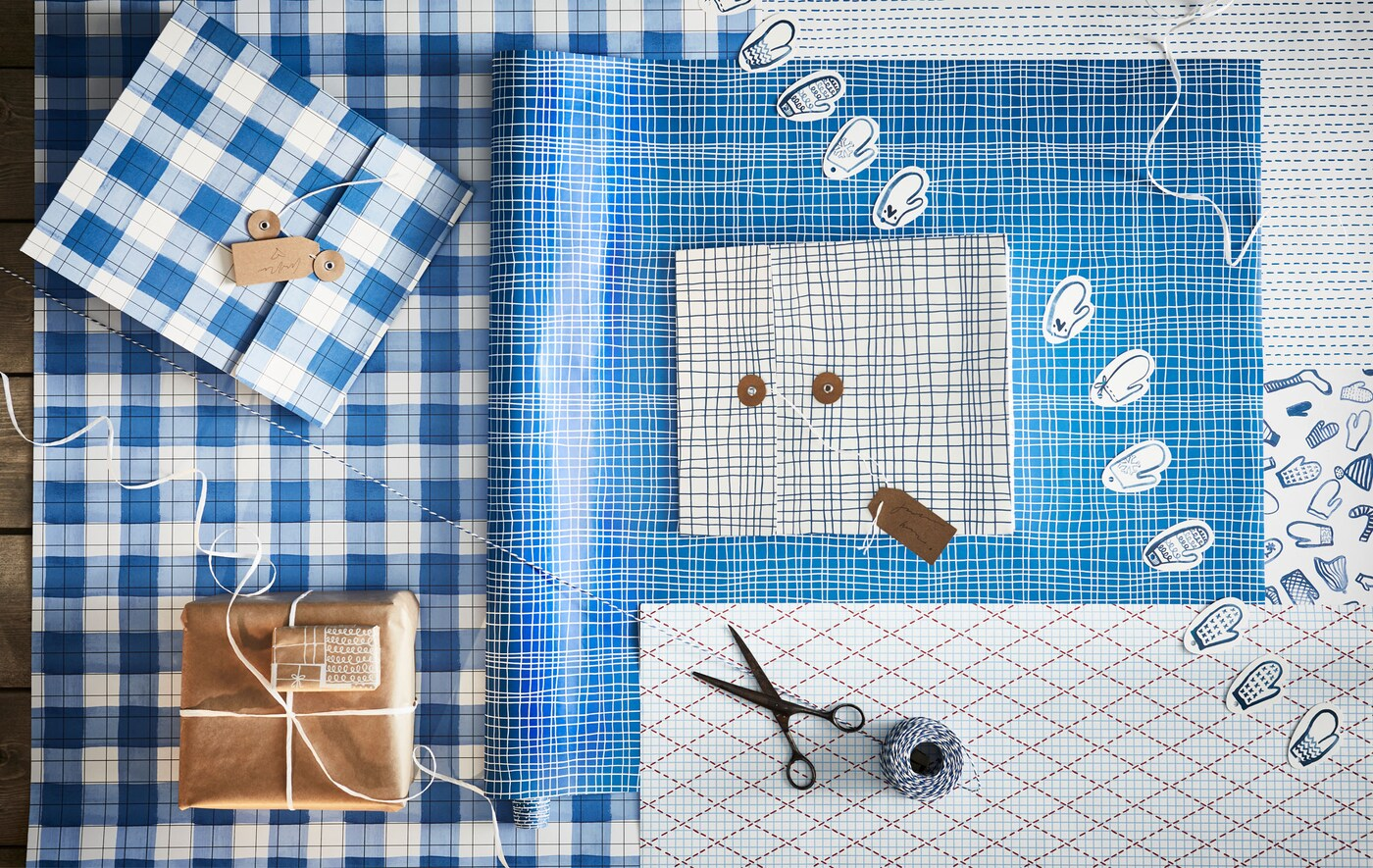 Stůl s rozbalenými balicími papíry a dalšími potřebami na balení dárků