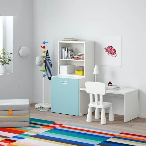 STUVA table and a chair is on the right hand side of a wardrobe, in front of a colourful rug.