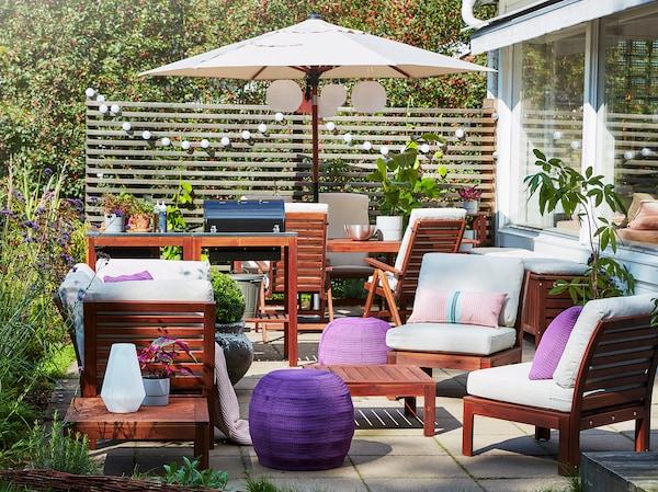 Štvormiestna súprava na sedenie a stôl z akácie, béžové vonkajšie vankúše, fialové sedadlá, ružová prikrývka a vankúše.