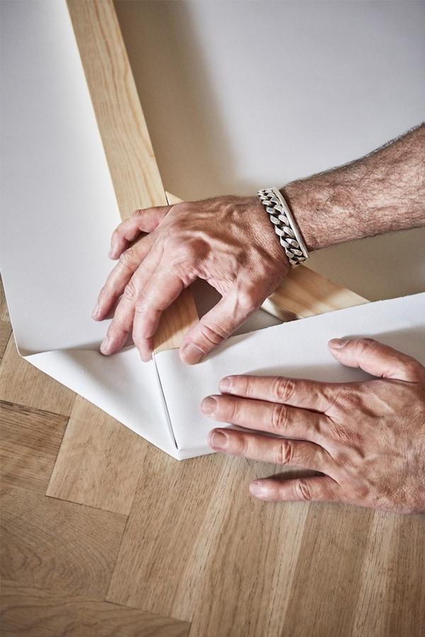 Su un pavimento in parquet, un uomo piega un pezzo di tessuto bianco sull'angolo di una cornice in legno - IKEA