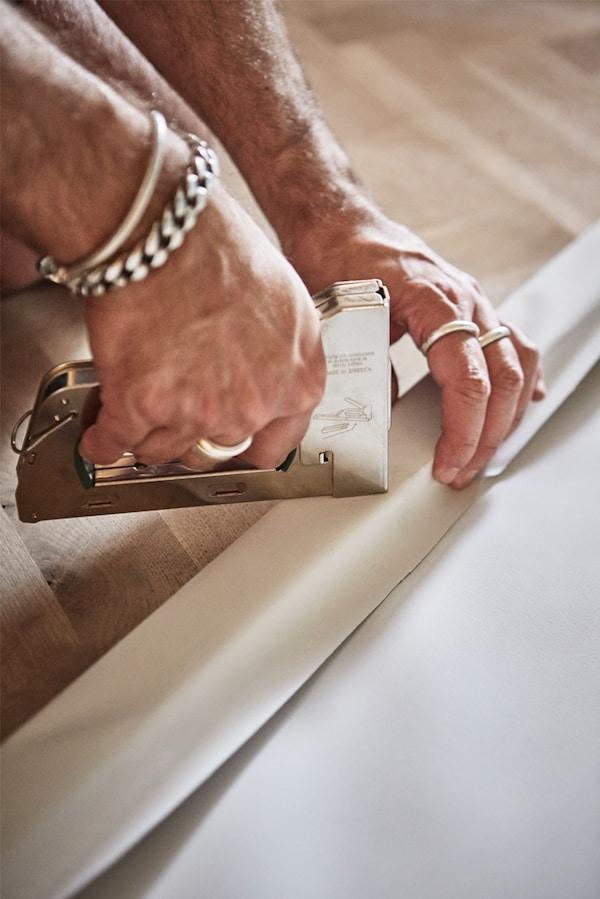 Su un pavimento in parquet, un uomo pinza un tessuto bianco a una cornice in legno con una pinzatrice - IKEA