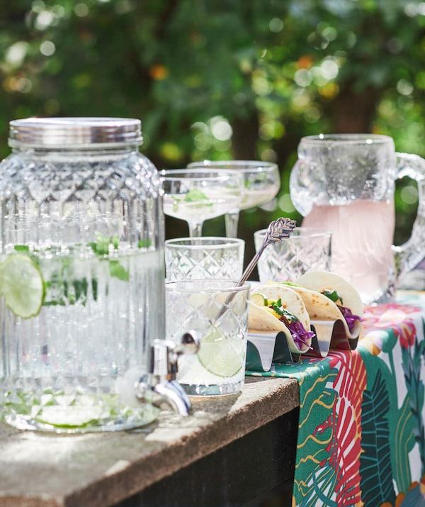 Su un tavolo in legno grezzo, un dispenser con rubinetto in vetro KALASFINT pieno d'acqua, coppe da champagne STORHET e dei tacos - IKEA