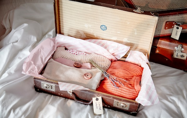 Suitcases make great storage space. They're made for carrying clothes and often take up a bit of room themselves, so using them as storage makes them doublty useful. Add some acid-free tissue paper lining if your bags are a little older and use some lavender or cedar blocks to keep away any bugs.