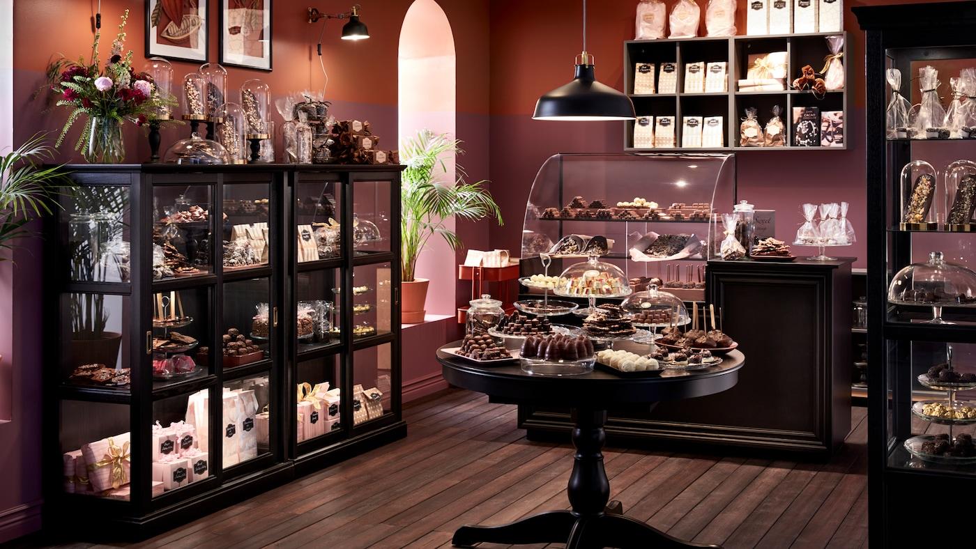 Suklaapuoti, jossa mustaksi värjätyt, lasiovelliset MALSJÖ-kaapit ja ruskeat seinät, kaapeissa erilaisia käärittyjä suklaita ja karkkeja.