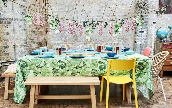 Summer party table with bright tablecloths, blue and green crockery set out, chairs and benches and a floral hanging garland.