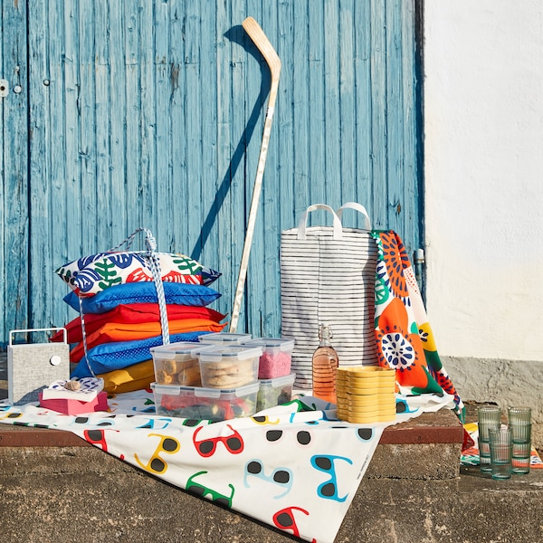 Summer party textiles, plates, finger food and a black and white KLUNKA laundry bag laying on some concrete steps outside.