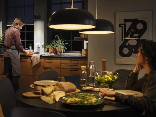 スマート照明機能のある大きなペンダントランプをつるしたキッチン。ディナーのためのテーブルセッティング。テーブルに着いた女性とシンクの前の男性。