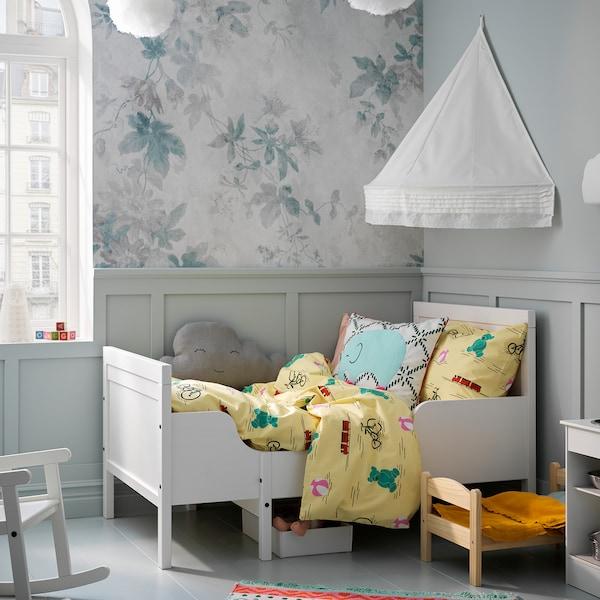 SUNDVIK produživ krevetni okvir u beloj boji, sa žutom posteljinom. Baldahin visi na zidu i kreira udobnu atmosferu.