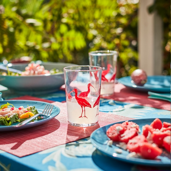 Sunlit table set outdoors with table and glassware in bold colors and patterns. Light dishes on the plates.