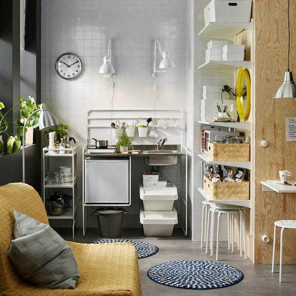 SUNNERSTA white mini-kitchen with portable induction hob and a small fridge, with a trolley and LACK wall shelves.