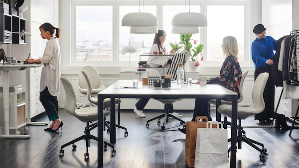 Sunny Office With People Working At A Conference Table And Standing Desk