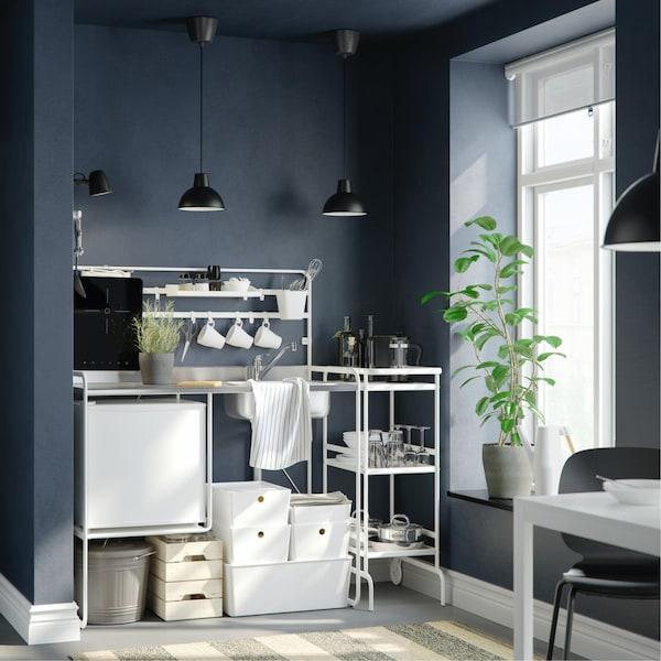 Supereenvoudige witte keuken tegen een zwarte muur en aan een raam