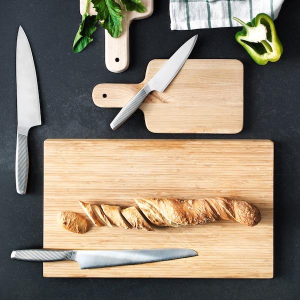 Superfície preta com três tábuas de cortar em madeira e três facas de cozinha. Em cima de uma tábua de cortar encontra-se um pão.