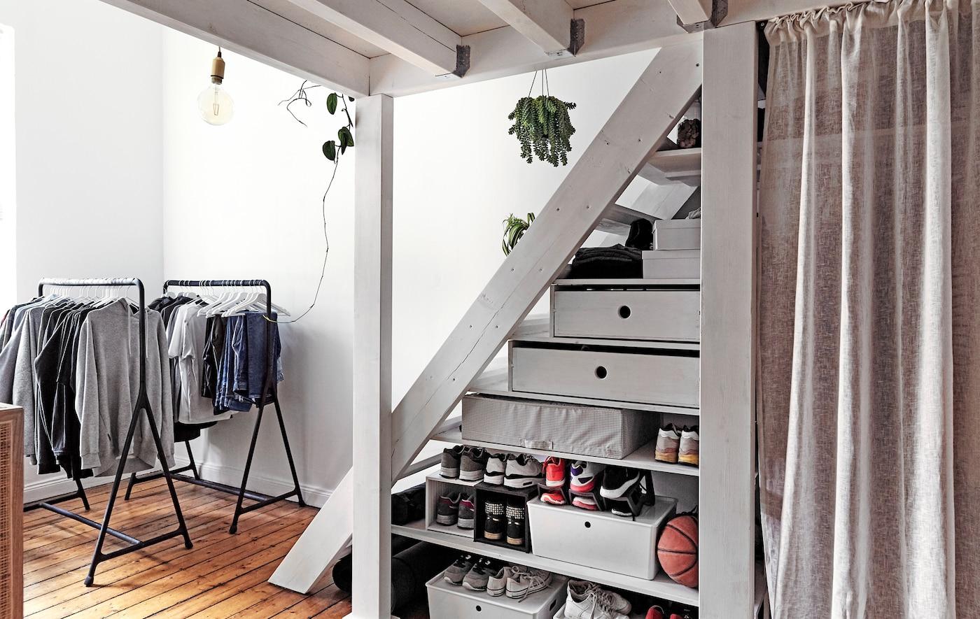 Suportes para cabides abertos e caixas de arrumação por baixo de um lanço de escadas.