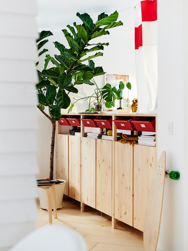 Sur le plancher d'une pièce blanche se trouve une rangée d'armoiresIVAR, qui servent aussi de paravent, qui combinent espaces de rangement ouverts et fermés.