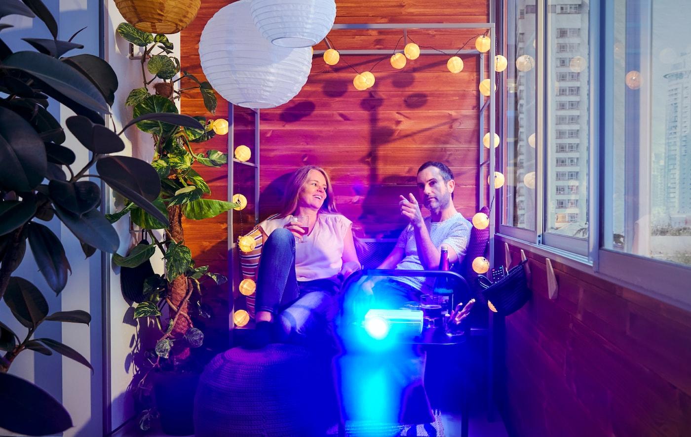 Sur un balcon, une femme et un homme assis sur un banc tonnelle, avec un projecteur allumé sur une table d'appoint devant eux.