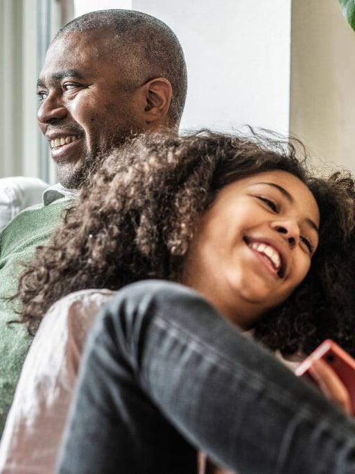 Sur un canapé, un père et sa fille se font des câlins en riant.