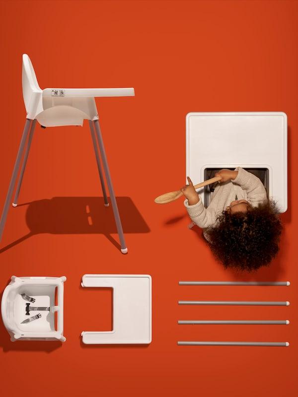 Sur un fond orange, une chaise haute ANTILOP et un éclaté de tous ses éléments vus d'en haut, y compris un bébé assis tenant une cuillère en bois.