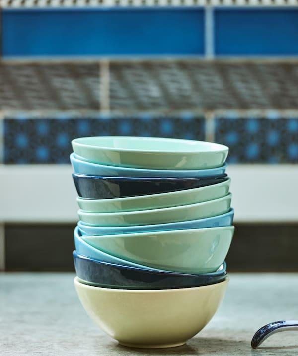 Sur un plan de travail en béton, devant des carrelages muraux bleus à motifs, une pile de bols dans des tons turquoise et bleu clair et foncé.