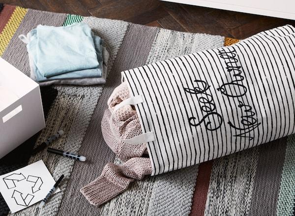 Sur un tapis, à côté d'une boîte, de stylos et d'étiquettes, un sac en toile contenant des vêtements sur lequel sont écrits les mots