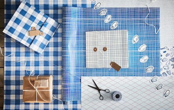 Sur une table, tout le nécessaire pour emballer des cadeaux: papier de différentes couleurs et motifs, ficelle, ciseaux, étiquettes et cadeaux emballés.
