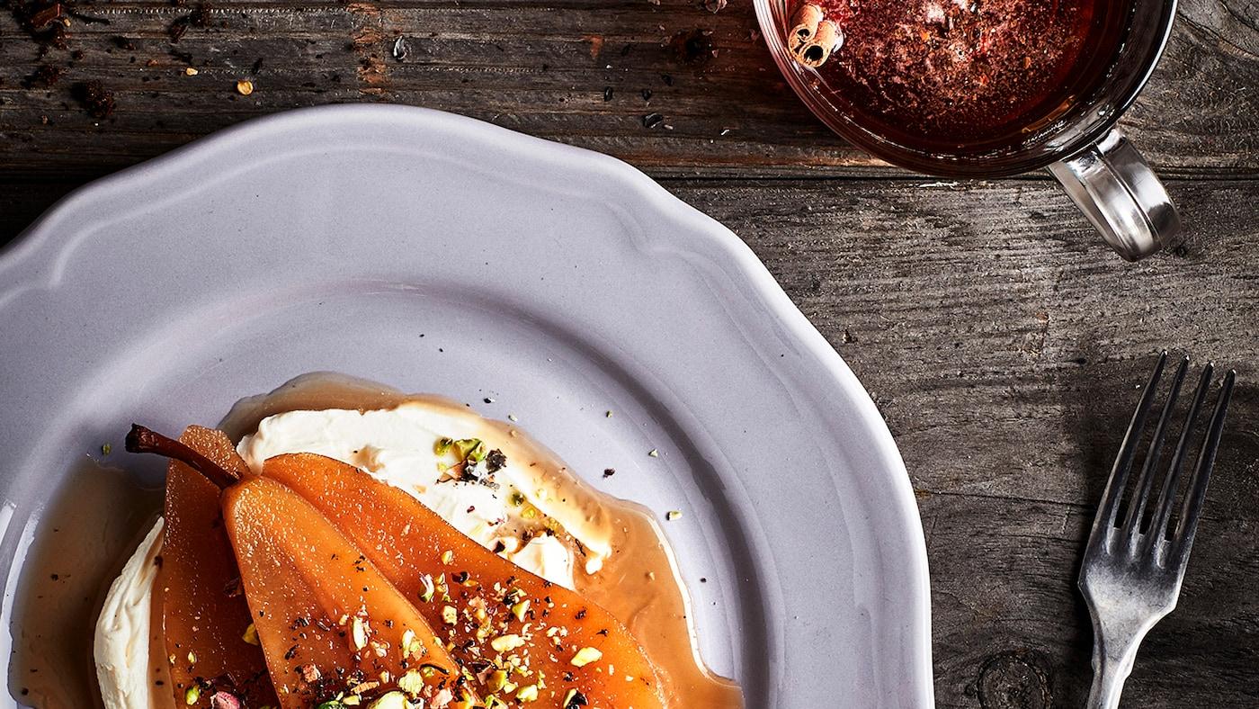 Surface d'une table en bois rustique avec un dessert à base de poires et de crème servi dans une assiette, avec une fourchette et une tasse de thé à côté.