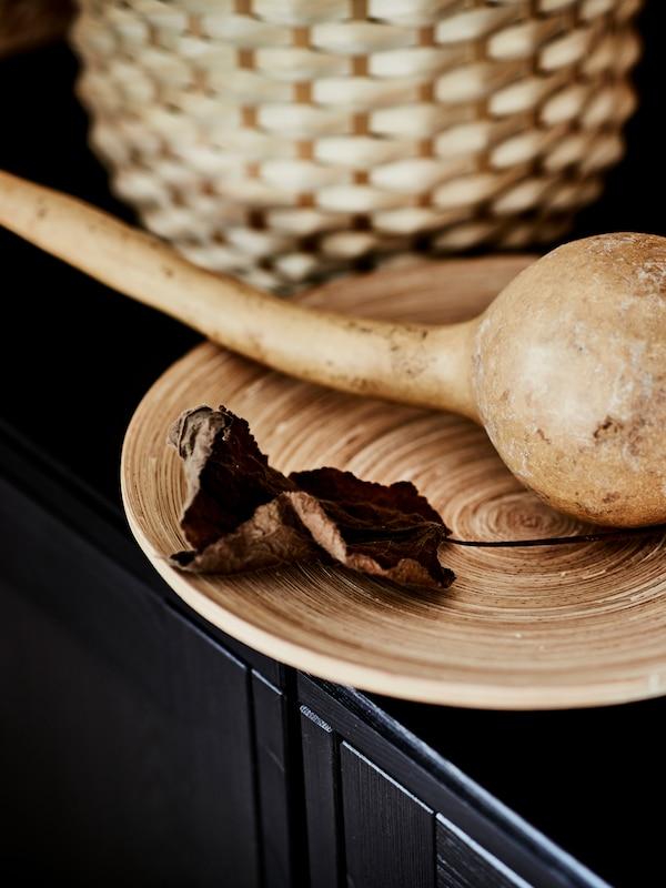 Sušená tekvica spolu so sušenými listami na bambusovom podnose HULTET, ktorý je umiestnený na tmavom povrchu.
