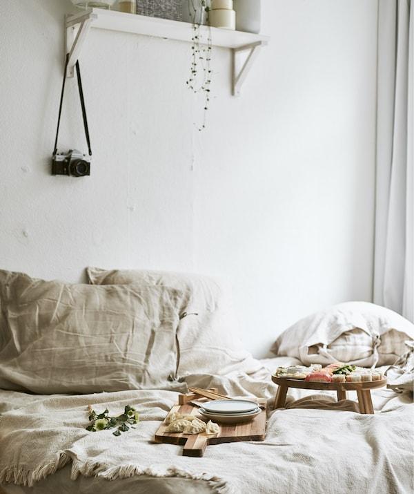 سوشي مقدم على ألواح خشبية على سرير بمفروشات سرير ذات ألوان محايدة ورف على الحائط الأبيض من أعلى.