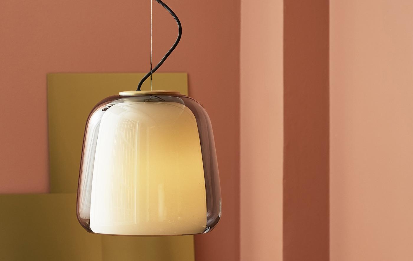 Suspension avec abat-jour en verre double épaisseur avec éléments en cuivre dans une pièce rose.