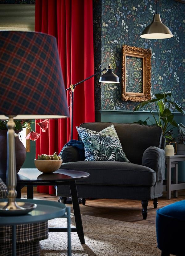 Suspensions FOTO dorées, lampadaire RANARP noir et abat-jours pour lampe de table RYRA en tartan bleu et rouge.