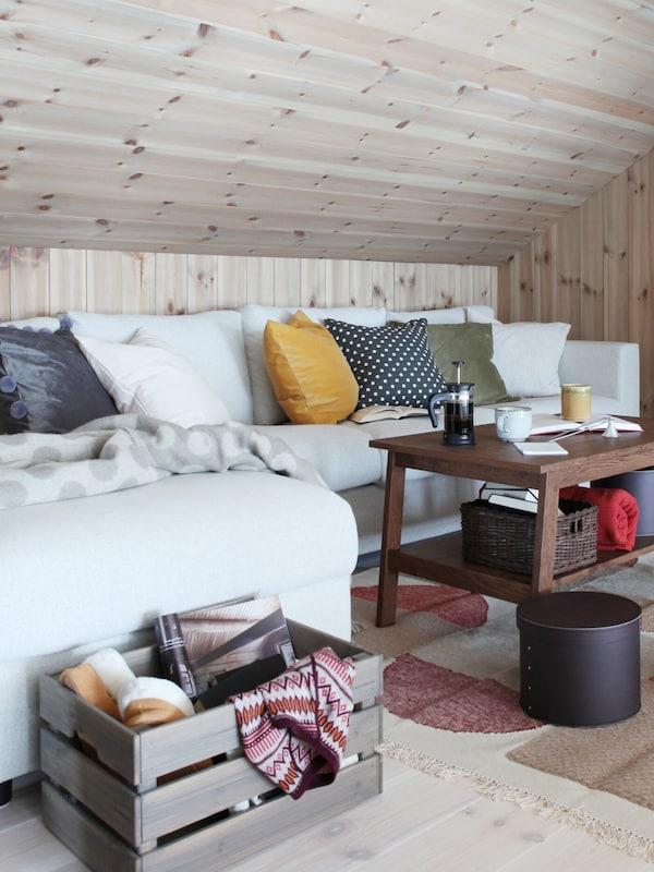 Suuri valkoinen sohva kaltevan katon alla. Sohvalla runsaasti tyynyjä.