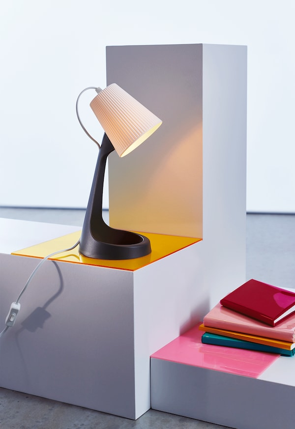 SVALLET work lamp on a stand, beside some books.