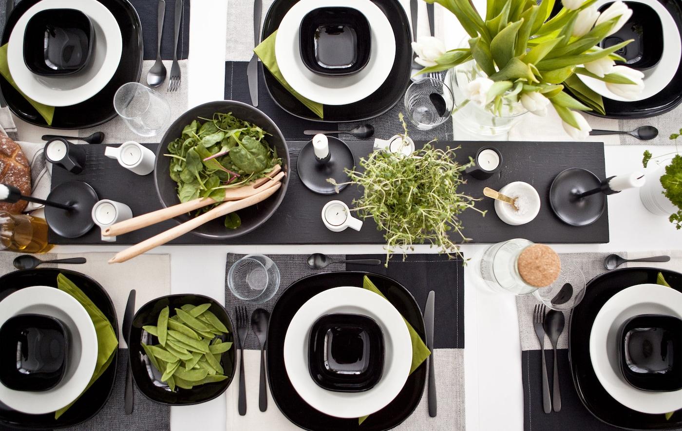 Svart og hvit borddekking med grønne innslag som planter, mat og servietter.