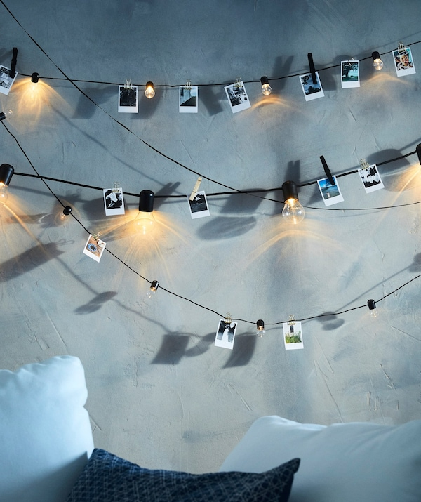 SVARTRÅ LED lighting chains hanging across a grey wall, with small illustrations clipped to the cords between the bulbs.