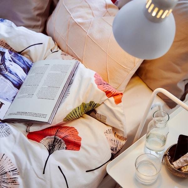 Свет от лампы падает на постельное белье с цветочным узором, подушки и книгу; на маленькой белой прикроватной тумбе рядом с кроватью стоят стаканы с водой и графин.
