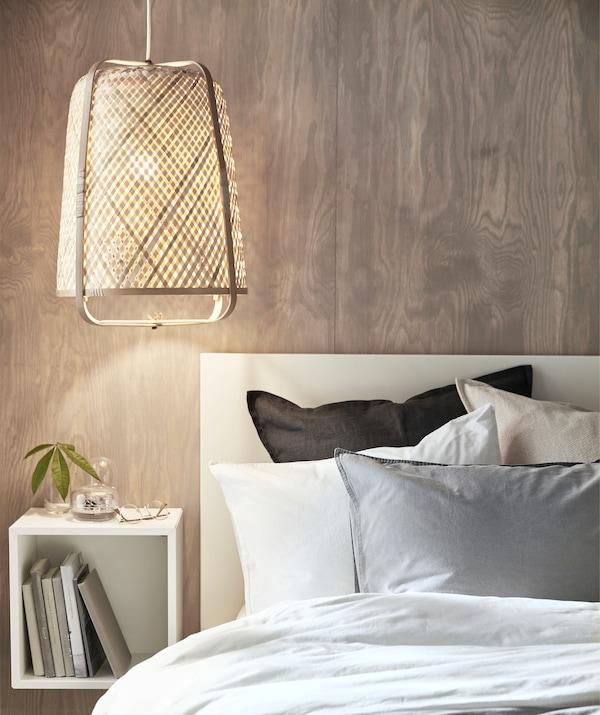 Светильник с бамбуковым абажуром, низко свисающий над кроватью, и квадратный модуль для хранения, закрепленный на деревянной стене позади.