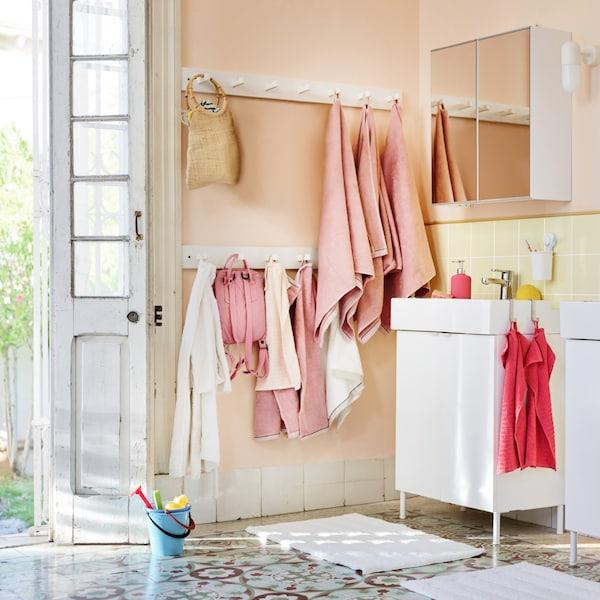 Světlá koupelna s bílými a růžovými ručníky, bílé skříňky  setting with various towels in both pink and coral, and bags hanging on the wall.