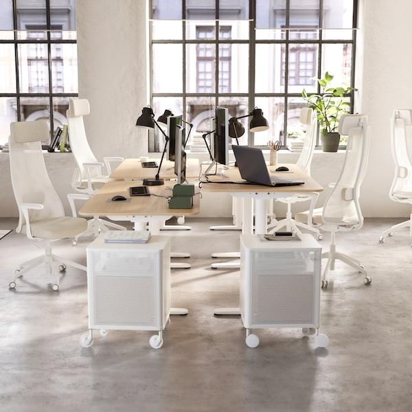 Světlá otevřená kancelář se čtyřmi psacími stoly BEKANT přisunutými ksobě, kde ukaždého stolu stojí bílá kancelářská židle ačerná pracovní lampa.