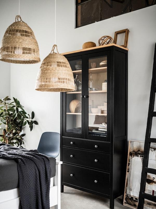 Svetlá spálňa s vysokou čiernou vitrínou HEMNES so sklenenými dvierkami, závesnými lampami TORARED, dekoráciami a rastlinou.