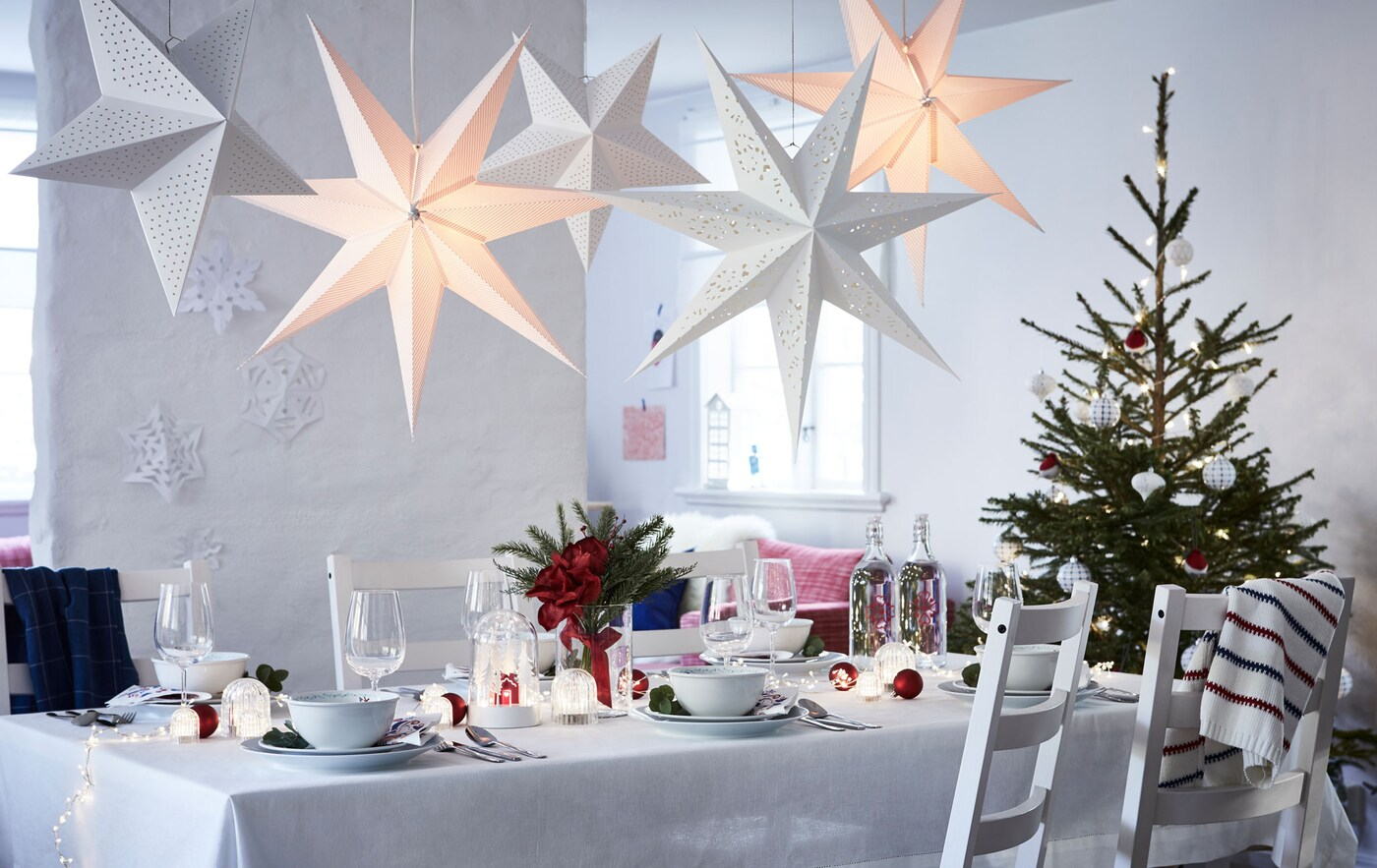 Светлая, большая, комната с минимальным набором мебели, в которой стоит длинный стол для праздничного ужина. С одной стороны стоит новогодняя елка, сверху висят бумажные звезды.
