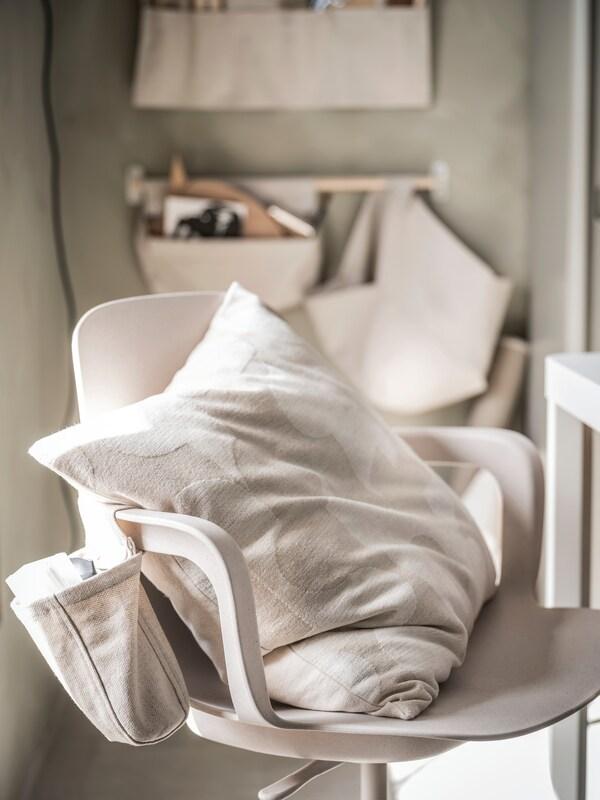 Světle béžová místnost, v popředí stojí béžová otočná židle ODGER. Na stěně v pozadí visí tři nástěnné úložné díly NEREBY v přírodní barvě, další je připevněn k područce otočné židle.