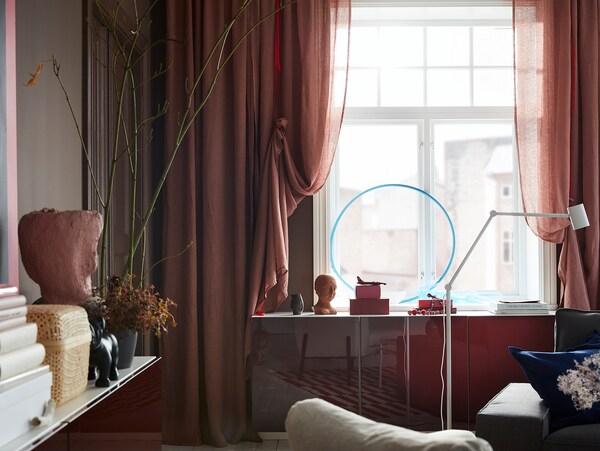Svetlé ružovohnedé závesy LEJONGAP sú doplnené červenými šnúrami a zavesené na okne.
