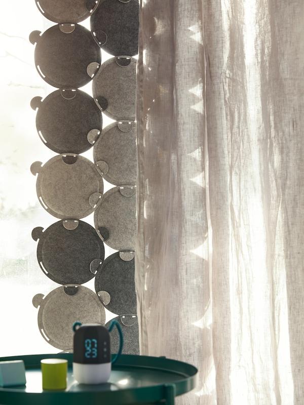 Svetlo ulazi kroz prozor, delimično pokriven ODDLAUG panelima koji apsorbuju zvuk i neprovidnom zavesom.